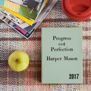 progress not perfection book on table with apple