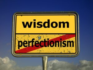 road sign that says wisdom with the word perfectionism crossed out